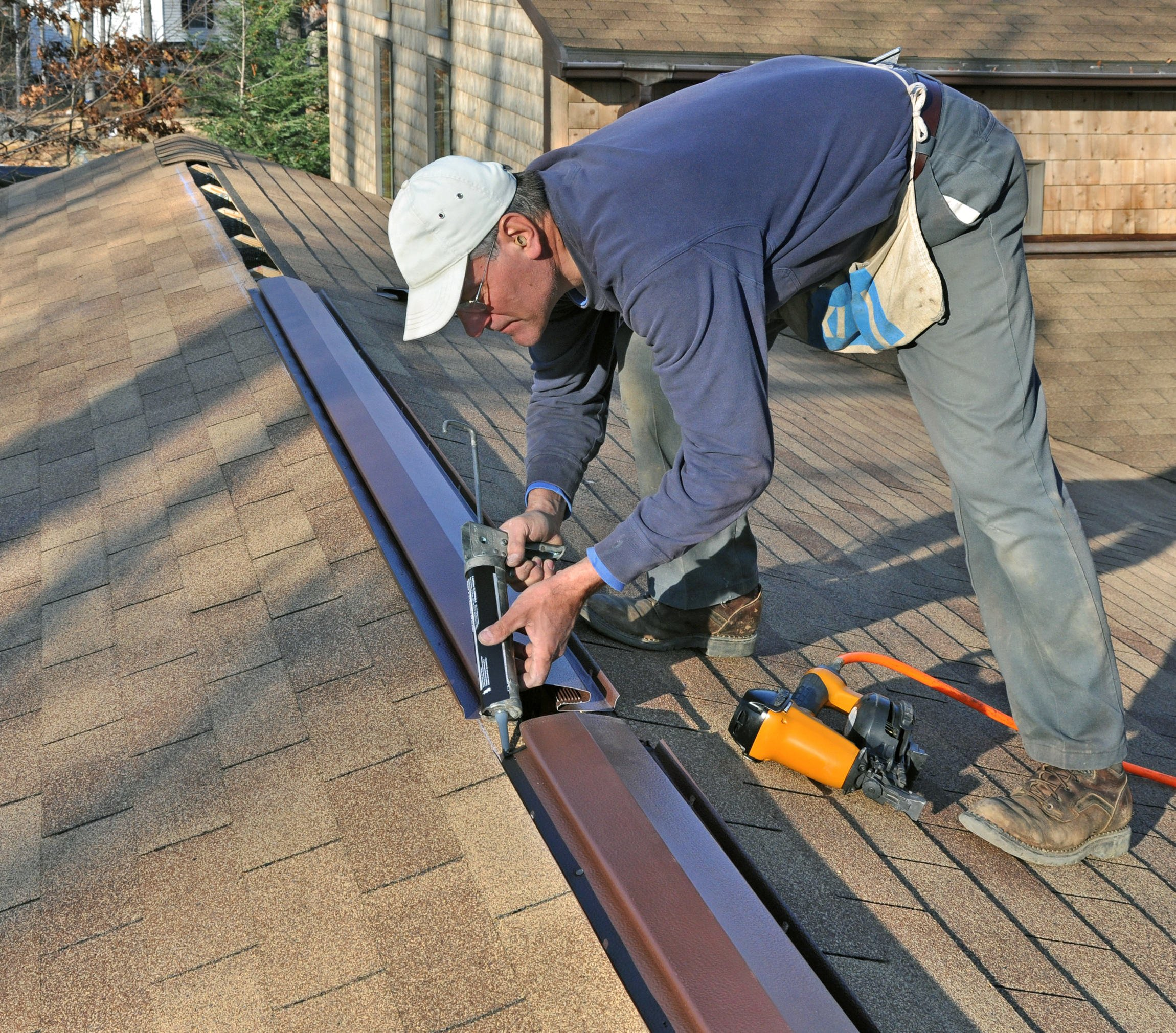 Carpenter applying caulk to ridge vent