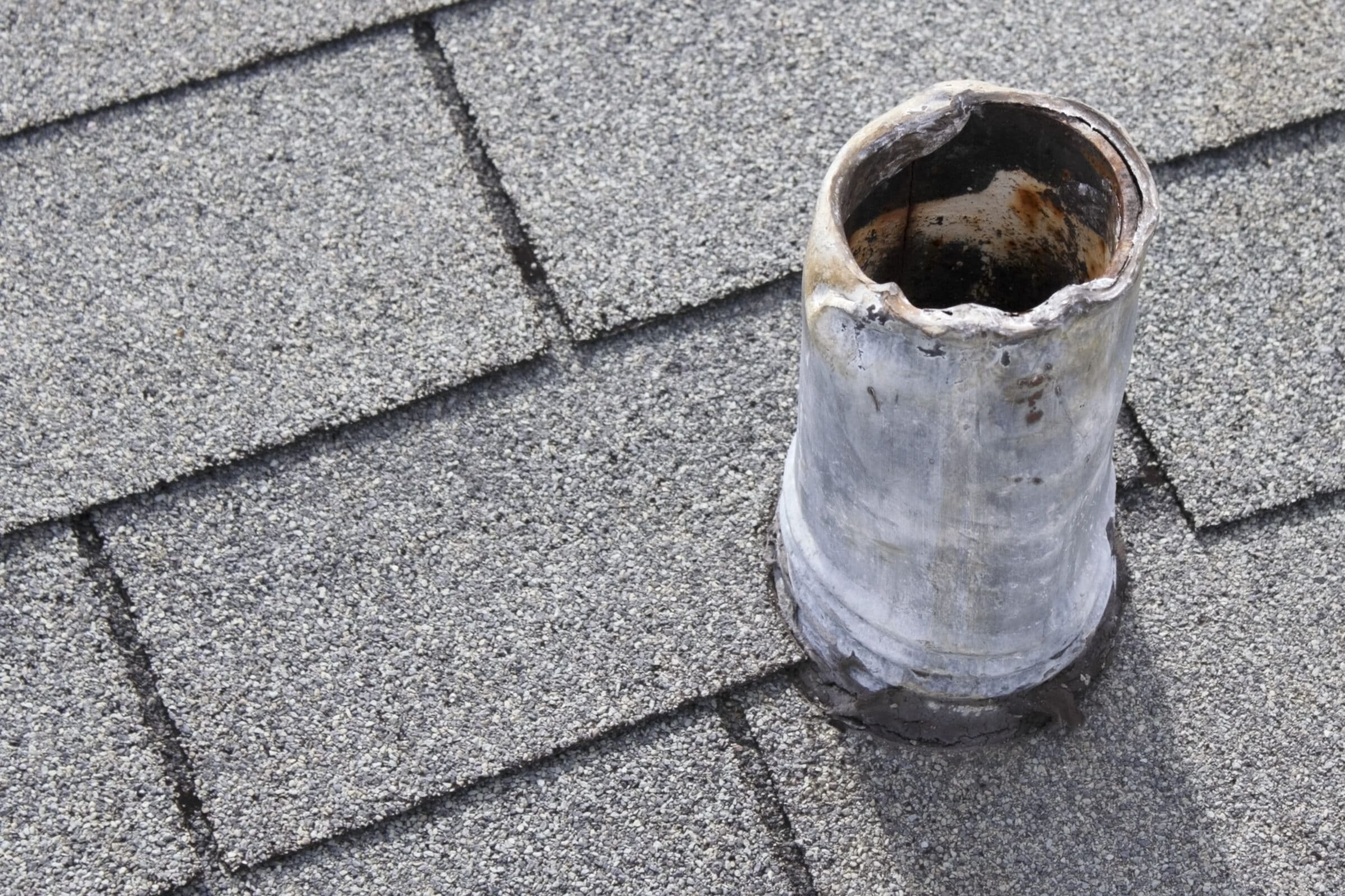 Residential short gray metal roof vent stack and black boot that shows sign of wear on top and bottom from snaking out the plumbing pipe in the past and that needs repair so there is no water damage.